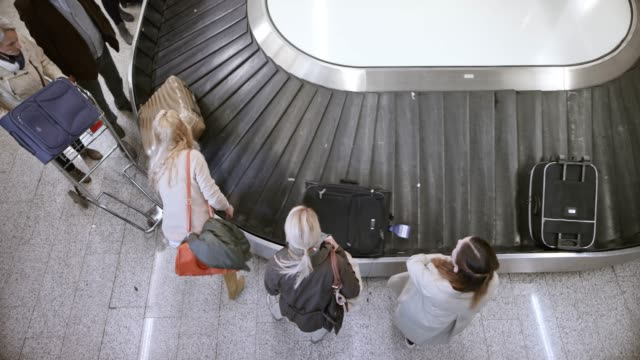above the passengers waiting for their luggage by the carousel at the airport - luggage stock videos & royalty-free footage