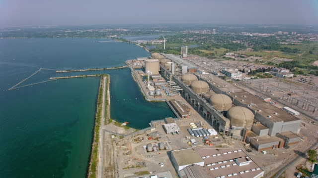 vídeos de stock e filmes b-roll de aerial above the pickering nuclear generating station on the shore of lake ontario, canada - central de energia nuclear