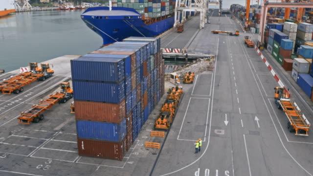 vidéos et rushes de aerial au-dessus de la route dans le terminal à conteneurs menant aux grues - container