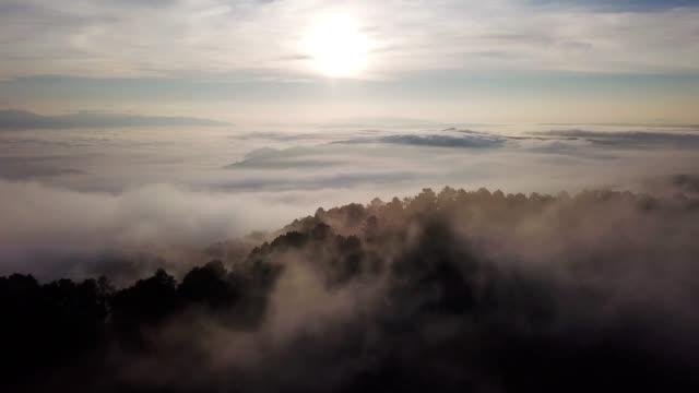 vidéos et rushes de au-dessus du ciel et les nuages avec le lever du soleil et de la brume sur la montagne - image dépouillée