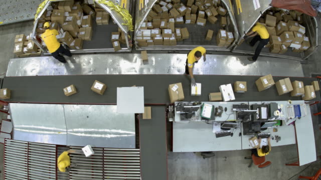 ld above the warehouse workers putting packages on the conveyor belt - conveyor belt stock videos & royalty-free footage