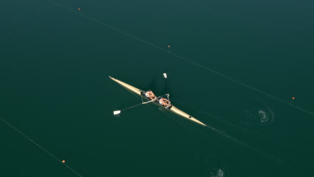 aerial above two athletes in a coxless pair gliding on a lake - scull stock videos & royalty-free footage