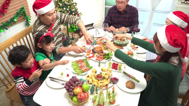 above view: celebrate moment of southeast asian multi-generation family, grandfather, grandmother, father, mother, daughter, son at dinner table with christmas full course food, grilled chicken, green, red food in a decorated home with tree and ornament. - 65 69 years stock videos & royalty-free footage