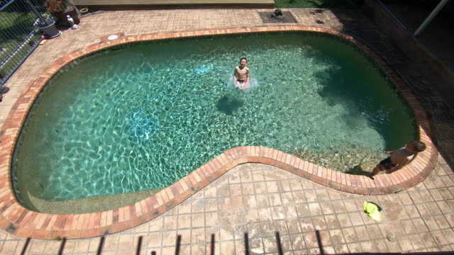 above view of a boy jumping in a swimming pool - swimming pool stock videos & royalty-free footage