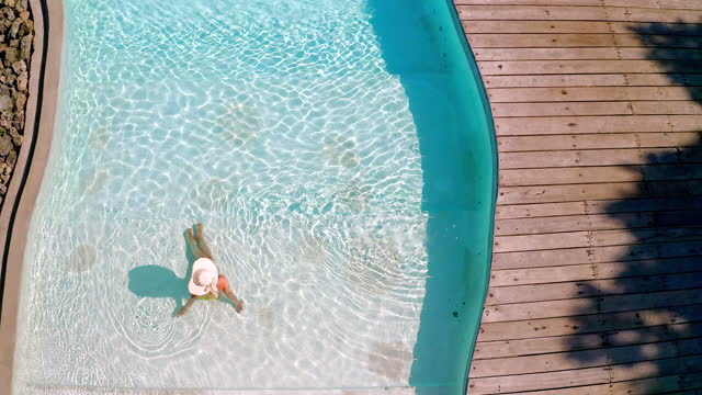 above view of carefree woman relaxing in swimming pool. - hat stock videos & royalty-free footage