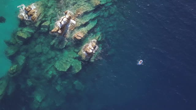 vídeos de stock e filmes b-roll de above view of small boat sailing near reefs - greece