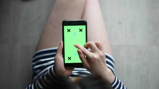 Por encima de la vista de la mujer uso de Smartphone, pantalla verde