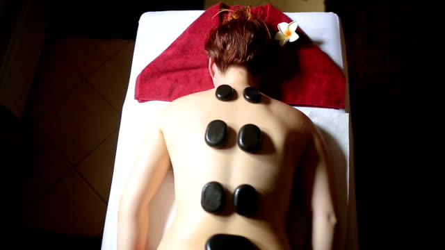 Above view of young woman during lastone therapy at spa