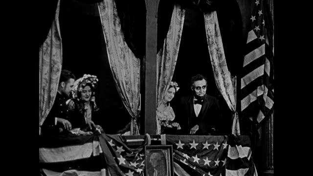 1865 Abraham Lincoln's (Joseph Henabery) assassination at Ford's Theater is witnessed by a woman (Lillian Gish) and other audience members