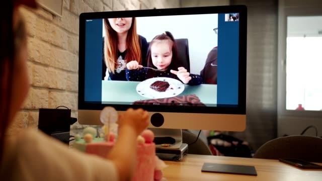 彼女は誕生日のための友人を持ることができないので、ビデオ通話を介して悲しい誕生日の女の子をchering海外の家族 - 誕生日点の映像素材/bロール