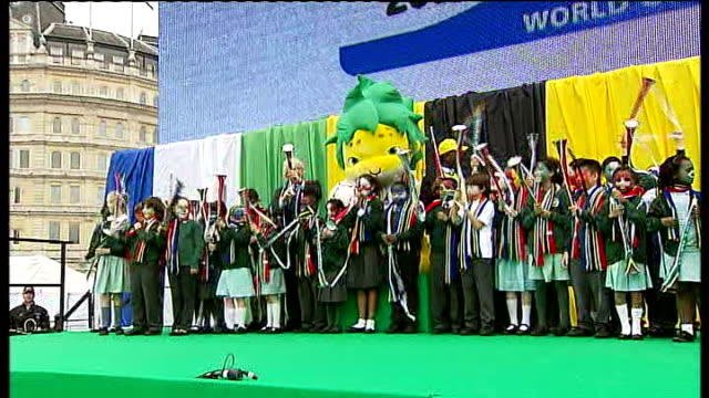 Absence of giant tv screens questioned R11061002 Long shot of Johnson on stage with schoolchildren posing for photocall as blowing vuvuzelas SOT...