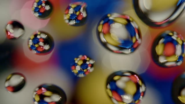 abstract background colored glitter balls rotating water drops on glass - water form stock videos and b-roll footage