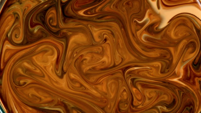 Abstract background. Mixing brown and orange liquids