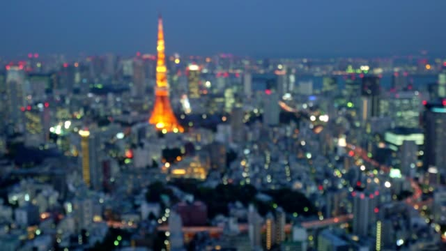 abstract background of tokyo city with tokyo tower illuminated at night - roppongi stock videos and b-roll footage