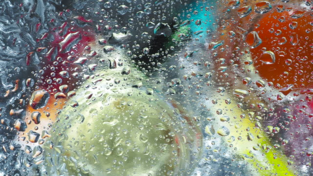 Abstract background with color liquids under wet glass