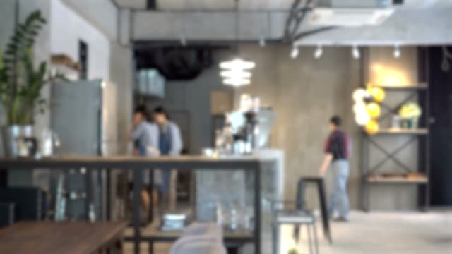 abstract blur shot of cafe or coffee shop interior with customer and barista working at the counter