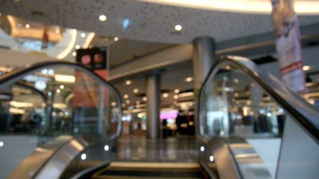 abstract blur shot of moving escalator in shopping mall with bokeh