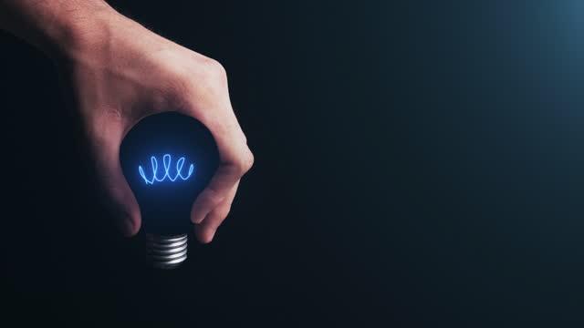 vídeos de stock, filmes e b-roll de imagem futurista conceitual abstrata de uma mão masculina segurando uma forma de lâmpada, representação de arte contemporânea tendo uma ideia brilhante, opinião, solução, filosofia, noção, mente, pensamento, palpite, percepção - advertisement