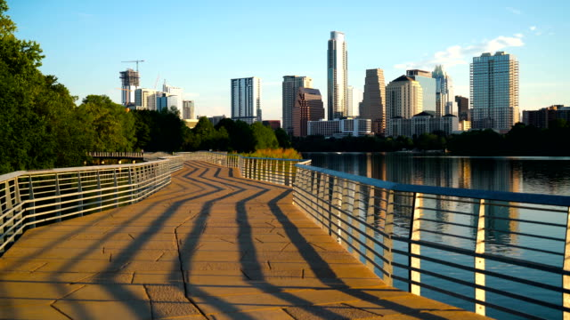 vídeos de stock e filmes b-roll de abstract shadows running lines down bridge austin texas town lake reflection skyline cityscape - town