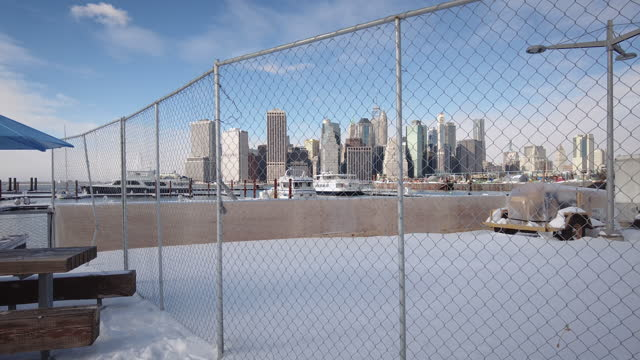 abstract visual framing. manhattan skyline behind a fence in brooklyn bridge park. filmed during the 2nd wave during the holidays. winter snow day in... - focus on foreground stock videos & royalty-free footage