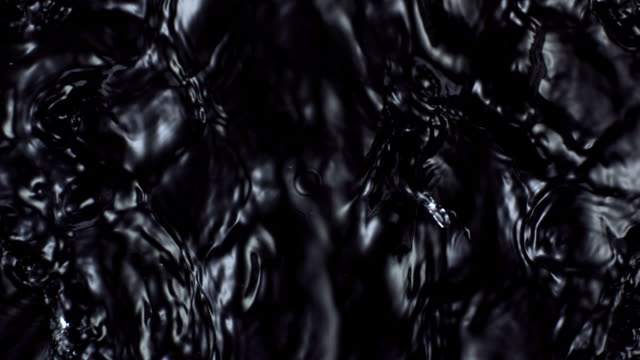 abstract water waves movement in black background, slow motion. - black colour stock videos & royalty-free footage