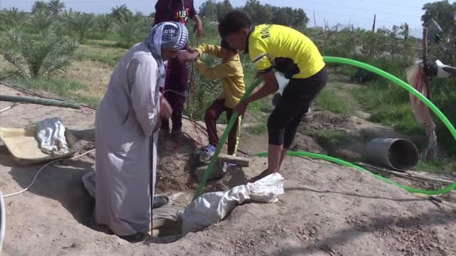stockvideo's en b-roll-footage met abu ali carefully crank starts a generator to pump water from a well out into his parched field in southern iraq - nasiriyah