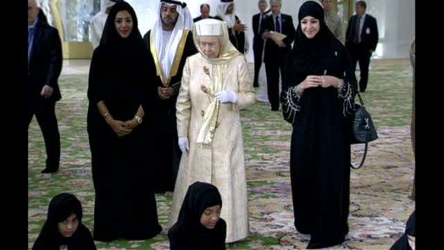Abu Dhabi EXT ***SOME Long Shot of Queen Elizabeth II walking with women to Sheikh Zayed Grand Mosque INT as being given tour of mosque and watches...