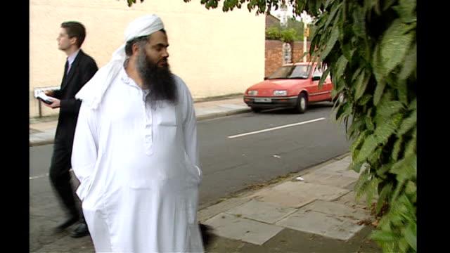 details of bail conditions tx north london ext abu qatada walking along street towards and past - アブ クアタダ点の映像素材/bロール