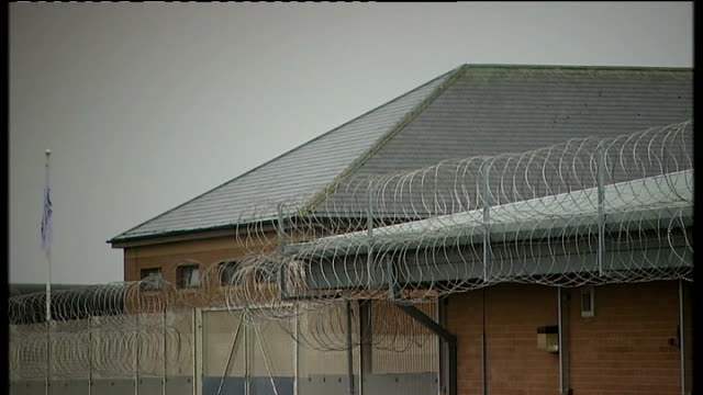 details of bail conditions worcestershire south littleton long lartin prison barbed wire fence and prison building long lartin sign windows behind... - アブ クアタダ点の映像素材/bロール