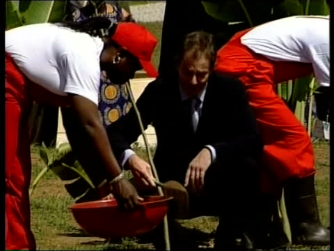 Abuja LMS MS Prime Minister Tony Blair MP scopping soil around base of newly planted tree LS Commonwealth Heads of Government Meeting venue building...
