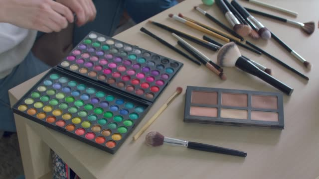 abundance of make up brushes and a eyeshadow pallet on a table - tutorial stock videos & royalty-free footage