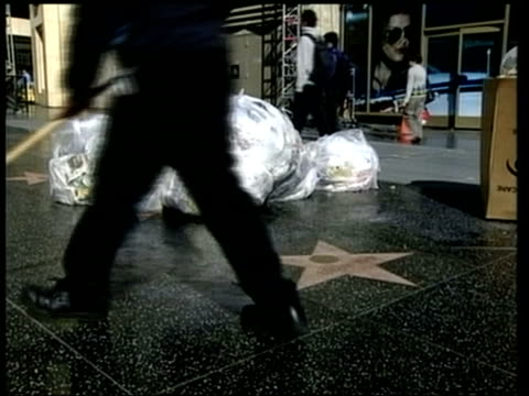 vídeos y material grabado en eventos de stock de california los angeles hollywood boulevard street covered in debris from oscars crowds side lms man along as sweeping up rubbish on morning after... - 2002