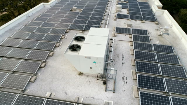 acc rooftop equipment with solar panel rooftop array a green display of rewnewable electricity creation - rooftop stock videos & royalty-free footage