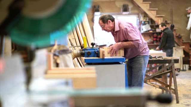 "accelerated ""time-lapse style"" video. the senior 60-years-old man, carpenter and sashman, craftsman, working with the industrial milling machine at the small wood factory - 65 69 years stock videos & royalty-free footage"