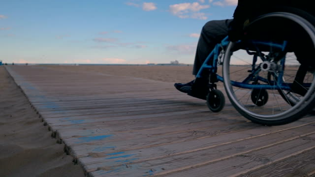 accessibility to the beach of a man in wheelchair - stock video - accessibility stock videos & royalty-free footage