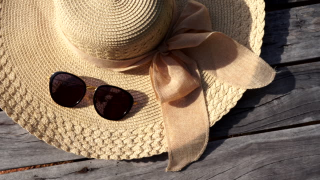 accessories for the holiday, sun glasses and sea hat on the wood bridge - cappello video stock e b–roll