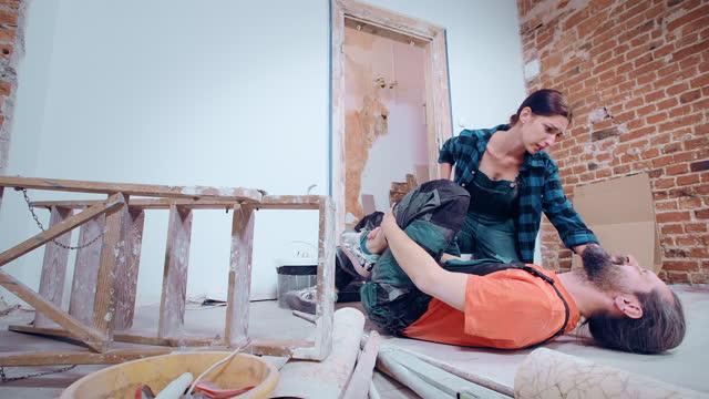 vidéos et rushes de accident lors de la rénovation de la maison. homme retenant son genou dans la douleur, femme recherchant l'aide - accident domestique