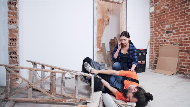 vidéos et rushes de accident lors de la rénovation de la maison. homme retenant son genou dans la douleur, femme appelant à l'urgence - accident domestique
