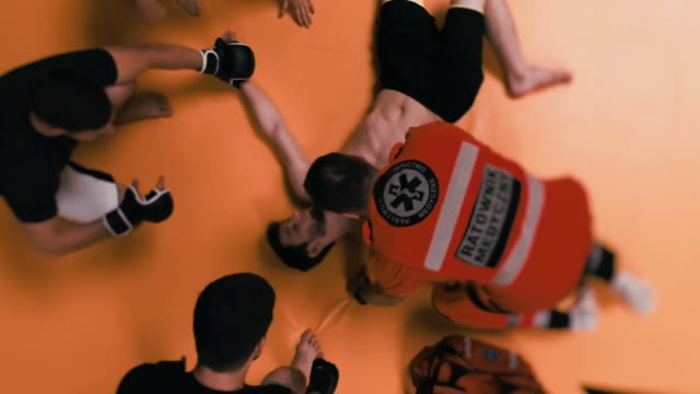 accident during martial arts training. paramedic helping unconcious fighter. aerial view - combat sport stock videos & royalty-free footage