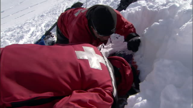 accident simulation team members dig a mannequin out of an avalanche path. - rescue stock videos & royalty-free footage