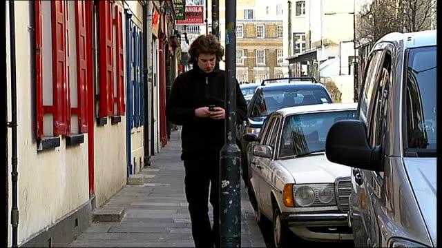 vidéos et rushes de brick lane pilot scheme to avoid texters hitting lampposts england east london brick lane ext reporter walking towards whilst texting on mobile phone... - heurter