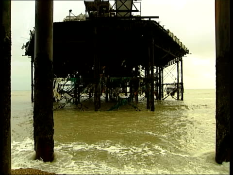 brighton west pier collapsing; gv people on brighton beach ruins of pier jonathan orell interviewed sot - discusses pier collapse - pier stock videos & royalty-free footage