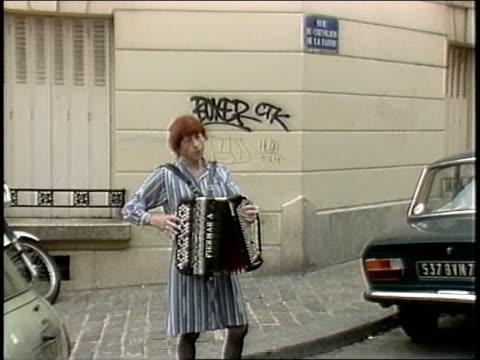 vídeos y material grabado en eventos de stock de accordian player on paris street between cars - acordeonista