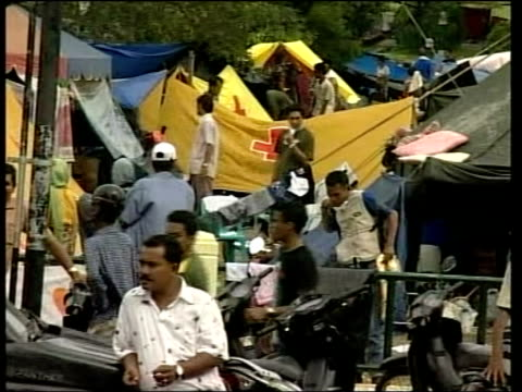 tsunami refugees sitting on truck towards tents in refugee camp man washing dishes in dirty brown water ms man with two children as rain falls in... - 2004 stock-videos und b-roll-filmmaterial