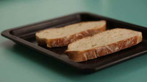 vídeos y material grabado en eventos de stock de aceite de oliva en tostada de pan de campo - tostada
