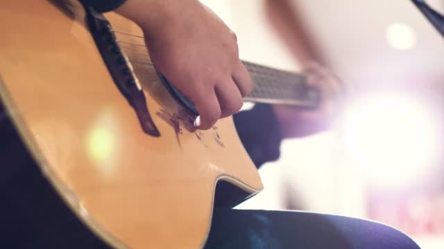 akustische gitarre in händen der musiker auf party. - country musik stock-videos und b-roll-filmmaterial