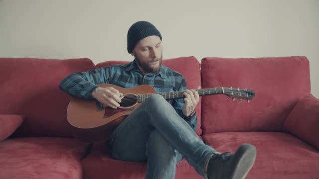 Acoustic guitarist playing guitar on his sofa