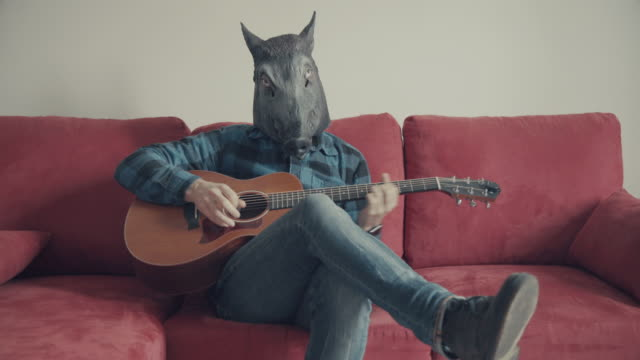 Acoustic guitarist with wild boar head playing guitar