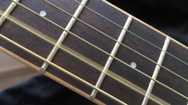 hölzerne akustikgitarre 4. & 5. saiten auf dem griffbrett - griffbrett stock-videos und b-roll-filmmaterial