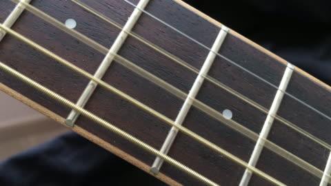 vídeos y material grabado en eventos de stock de guitarra acústica madera cadena jugando en diapasón - cordel